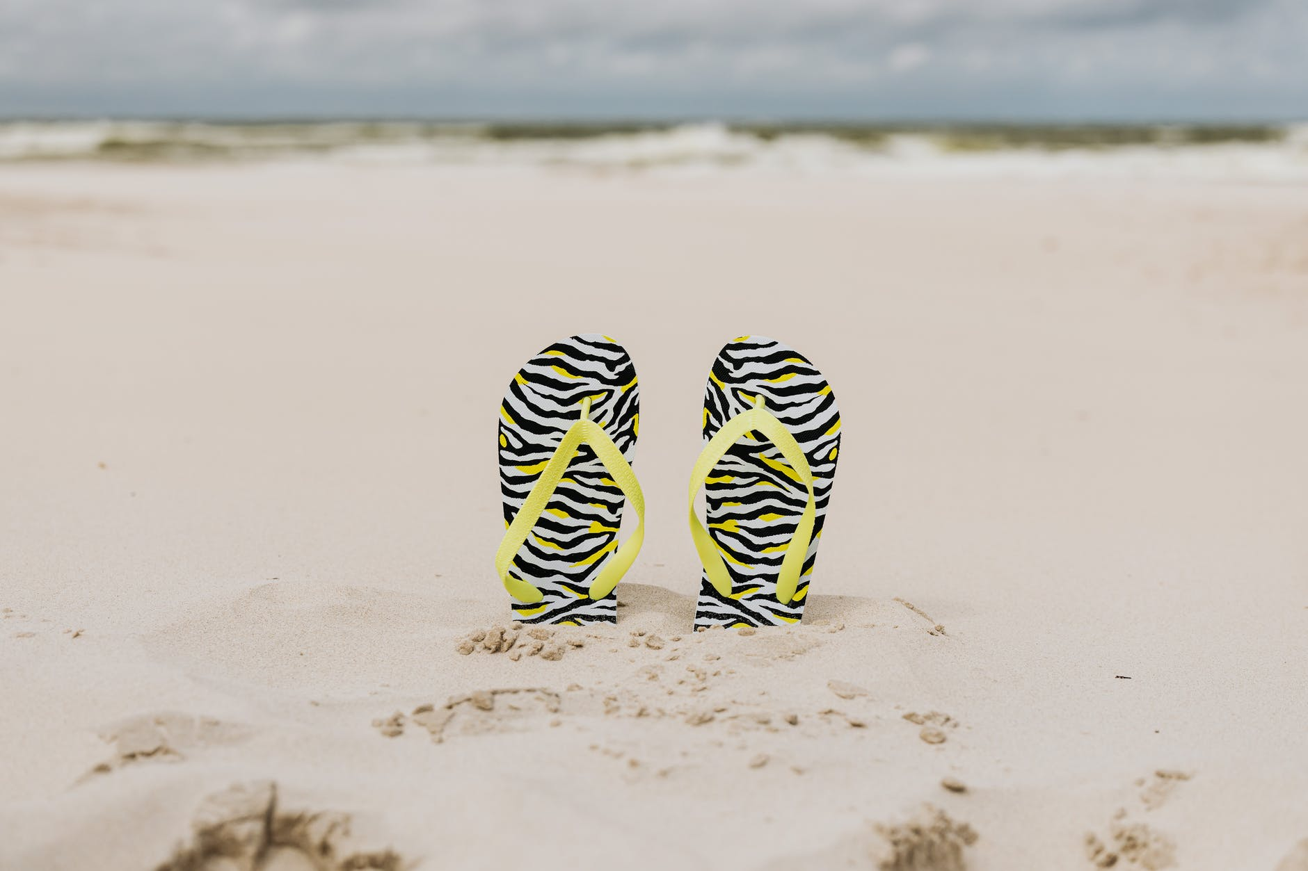 black and green stripe flip flops on white sand